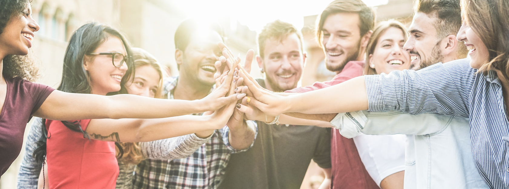 Young happy people stacking hands outdoor – Diverse culture students celebrating together – Youth lifestyle, university, relationship, human resorces, work and friendship concept – Focus on hands